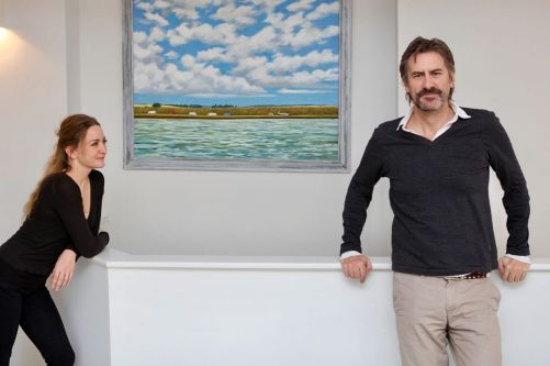 Anna and James Innes-Smith in front of a painting by Tim Fargher. Image: © Eliza O'Hara